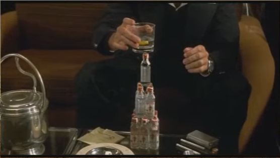 movie character drunkenly stacking gin bottles